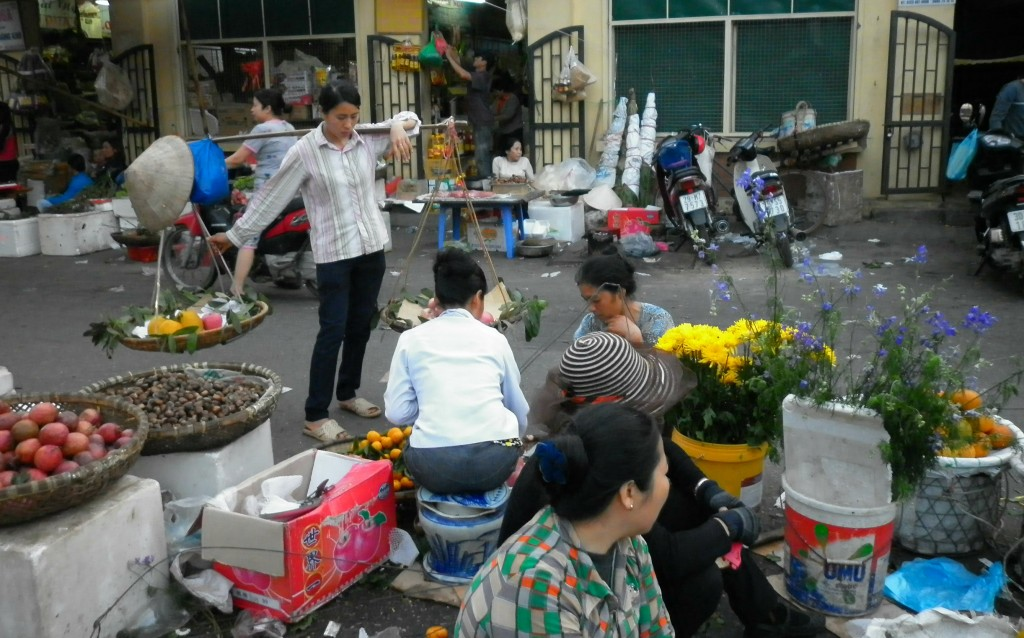 "Saleswomen in the Dong Xuan Market in the Old Quarter of Hanoi. One woman balances a shoulder yoke, or ""don gahn"", full of fresh mangoes."