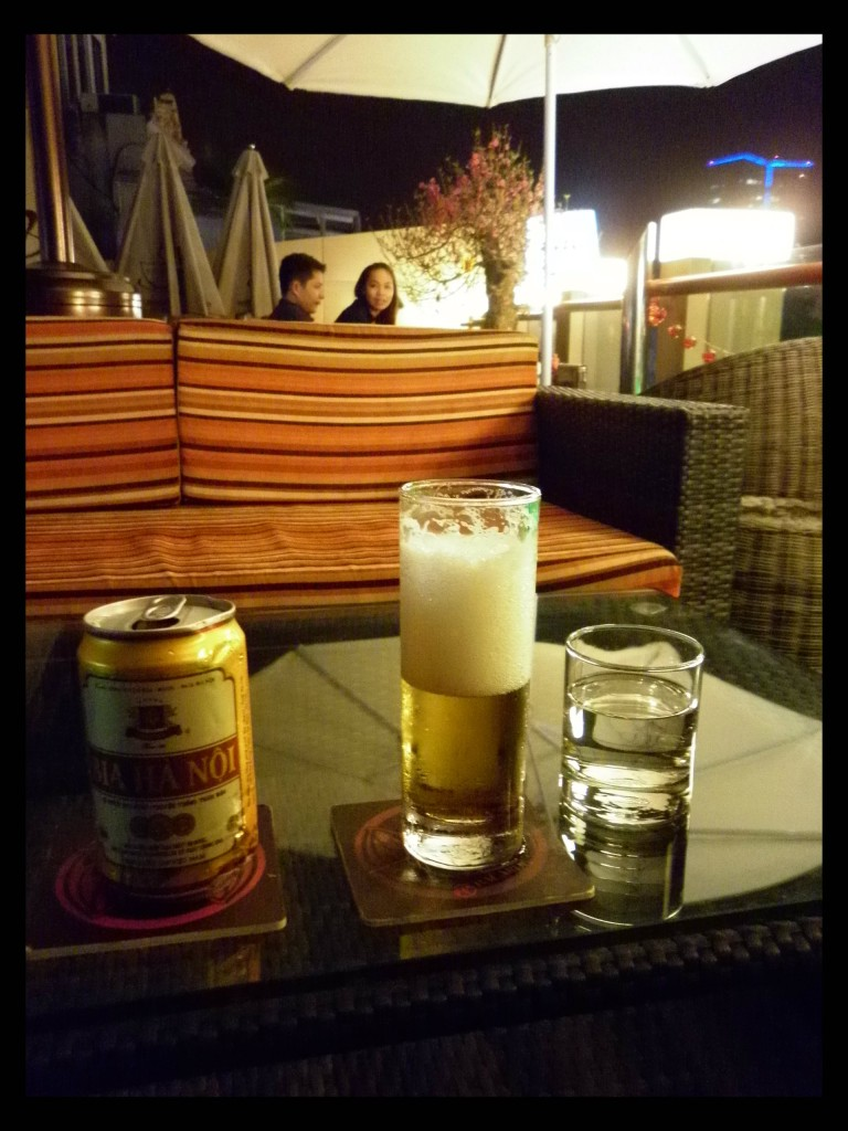 "Bia Ha Noi, a pale lager and the most popular brew in the region often as cheap as water.  The ice in my glass has already melted. On the rooftop of ""Feel It Cafe"" in Hanoi."