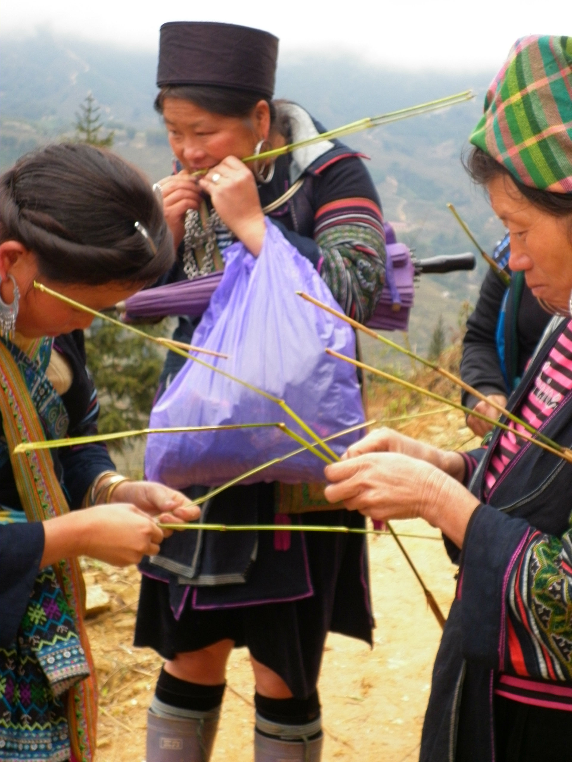 Hmong women in Sapa, in the far north of Vietnam, follow tourists persuading them to buy small handmade items.  These women are making small bamboo grass animals.