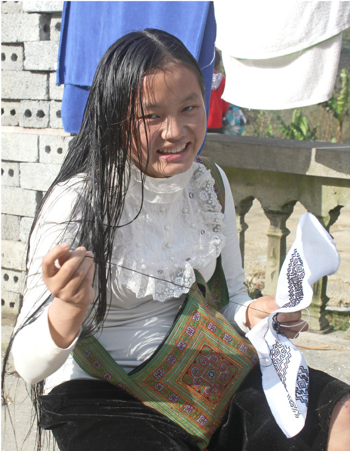 A young woman in Northern Vietnam weaves traditional fabric to sell to tourists in town.  Photo credit: Tom Watt